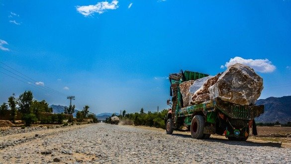 Trucks carry marble from a mountain to a factory in Mohmand Agency in May. [Alamgir Khan]