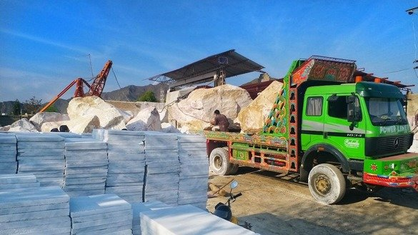 Workers unload a truck at a marble factory in Mohmand Agency in May. [Alamgir Khan]