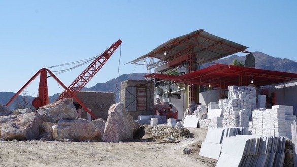 A crane loads a marble rock onto a cutting machine at a marble factory in Mohmand Agency in May. [Alamgir Khan]