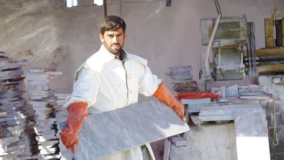 A factory worker holds a slab of processed marble in Mohmand Agency in May. [Alamgir Khan]