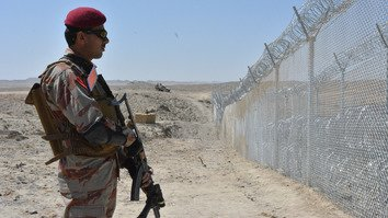 A Pakistani soldier stands guard at the fence along the Pakistani-Afghan border in Balochistan May 8. [Banaras Khan/AFP]