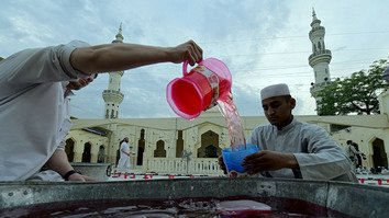 Pakistani volunteers serve sweet drinks to Muslims breaking their fast at a mosque in Peshawar May 17, the first day of Ramadan. [Abdul Majeed/AFP]