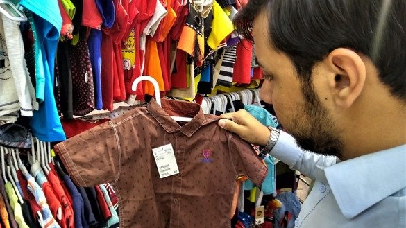 A customer in Rawalpindi buys a child's shirt June 10 for Eid ul Fitr. [Syed Abdul Basit]