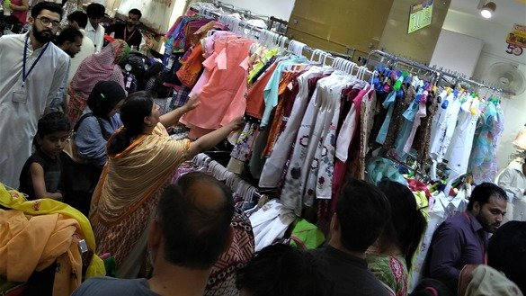 A woman shops for girls' clothes in Rawalpindi June 10 ahead of Eid ul Fitr. [Syed Abdul Basit]