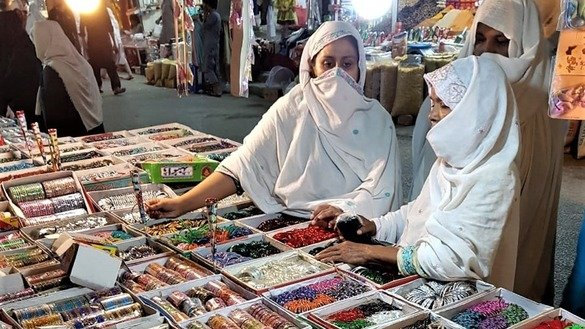 Women look at an array of bangles for sale in Nowshera June 9. [Syed Abdul Basit]