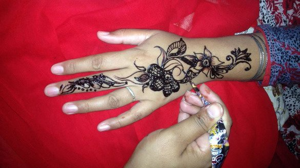 A woman has her hand painted with henna in Islamabad on June 12 ahead of Eid ul Fitr. [Syed Abdul Basit]