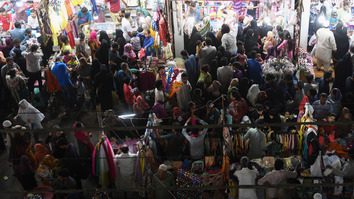 Pakistanis shop at a market June 13 early in the morning in Karachi. Police throughout Pakistan have stepped up security measures for Eid ul Fitr, which starts June 16, especially in crowded public areas. [Asif Hassan/AFP]