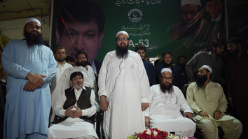 "Hafiz Saeed, leader of the militant group Jamaat-ud-Dawa (JuD) Hafiz Saaed (centre), speaks during the inauguration ceremony of JuD's election office in Islamabad June 21. Pakistan began acting against JuD and its affiliates after the FATF said it would add the country to its ""grey list"" in February. [Aamir Qureshi/AFP]"