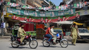 Pakistani youth July 16 in Rawalpindi drive along a road beside campaign posters for the July 25 general election. WhatsApp is combating fake news that could mislead voters. [FAROOQ NAEEM/AFP]