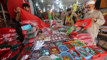 A shopkeeper at the Qissa Khwani bazaar in Peshawar sells flags, badges and caps of various political parties July 20. [Javed Khan]