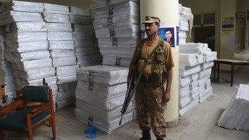 A Pakistani soldier stands guard next to polling materials before handing them over to polling staff in Lahore July 22. [Arif Ali/AFP]