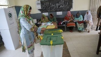 An election official seals ballot boxes before polls open in Islamabad July 25. [Aamir Qureshi/AFP]