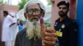 An elderly man shows his inked thump after casting his vote outside a polling station during general election in Lahore on July 25, 2018. [Arif Ali/AFP]