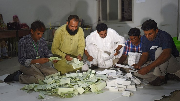 Pakistani election officials count ballots at a polling station in Karachi July 25. [Rizwan Tabassum/AFP]