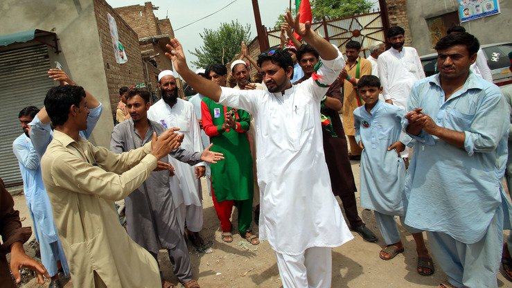 Supporters of PTI chairman Imran Khan dance in the streets of Peshawar after hearing the initial results of the elections on July 26. [Shahbaz Butt]