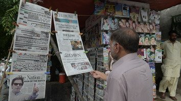 Pakistanis read morning newspapers July 26 in Islamabad, one day after the general election. [Aamir Qureshi/AFP]