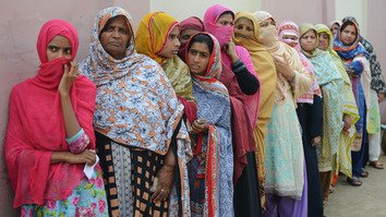 Women stand in a queue as they wait to cast their vote outside a polling station in Lahore on July 25, 2018. [Arif Ali/AFP]