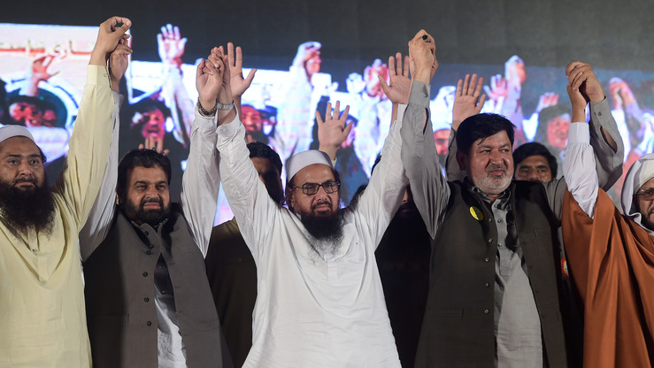 Hafiz Saeed (centre), the founder of a widely recognised terrorist group, raises arms with members of his newly formed political party, Allah-o-Akbar Tehreek, as they attend a campaign meeting in Islamabad July 21. [Aamir Qureshi/AFP]