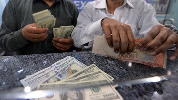 Pakistan is taking steps to counter money laundering and terror financing, officials say. Pictured here, money dealers count Pakistani rupees and US dollars at a currency exchange in Islamabad March 12, 2014. [AAMIR QURESHI/AFP]