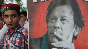 A supporter of Pakistan Tehreek-e-Insaf (PTI) stands next to a poster of PTI leader Imran Khan in Islamabad July 26. [Aamir Qureshi/AFP]