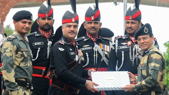 Pakistani Wing Commander Bilal (third from left) presents sweets to Indian Border Security Force Commandant Sudeep (right) during a ceremony to celebrate Pakistan's Independence Day at the India-Pakistan Wagah border post August 14. [Narinder Nanu/AFP]