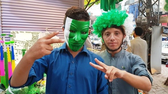 Two residents of Peshawar purchase different costumes to celebrate Independence Day August 14. [Danish Yousafzai]