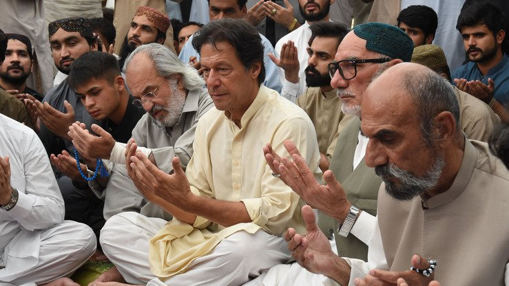 Pakistan Tehreek-e-Insaf party leader Imran Khan (left) prays with Aslam Raisani on July 15 in Quetta. Aslam is the elder brother of Siraj Raisani, a candidate for a Balochistan Provincial Assembly seat who was killed in a July 13 suicide bombing in Mastung. [Banaras Khan/AFP]
