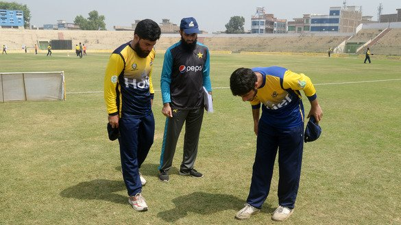 Captains of two cricket teams examine the result of a pre-match coin toss in Peshawar August 31. [Shahbaz Butt]