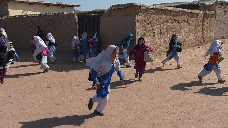 Afghan refugee girls run after school at a refugee camp on the outskirts of Islamabad February 1. [Aamir Qureshi/AFP]