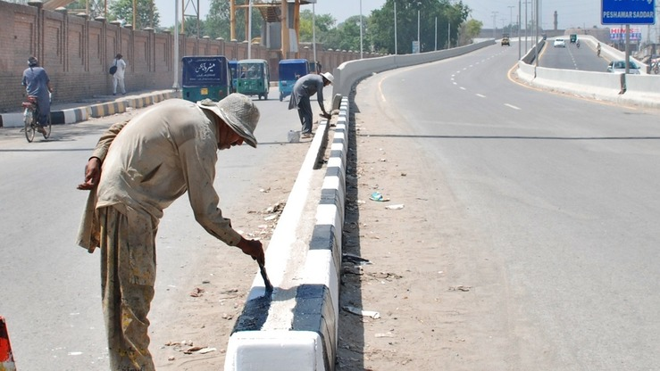 Workers paint a roadside in Peshawar Saddar Bazaar in April. The Pakistani government launched the Clean Green Pakistan campaign October 8 to end pollution and to ensure a clean environment. [Javed Khan]