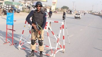 A policeman in Peshawar, Khyber Pakhtunkhwa (KP), stands guard on Ring Road November 3. KP will soon be deploying its police force in the tribal areas that recently merged with to become part of the KP. [Javed Khan]