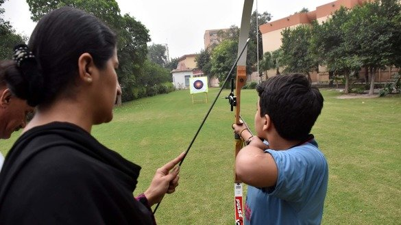 Sara Khan teaches a young student to how to use a bow and arrow in Peshawar in November. [Muhammad Shakil]