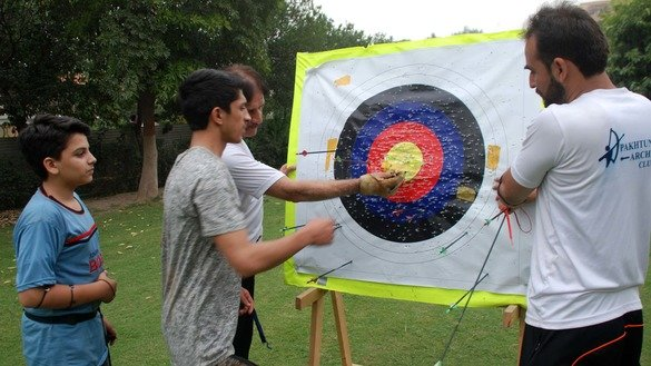 Archery students in Peshawar examine the target after training in November. [Muhammad Shakil]