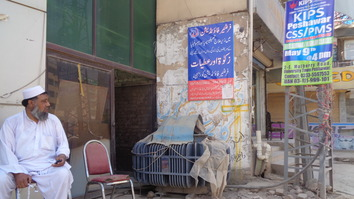 A man in Peshawar sits in front of a poster for a charity on February 13. [Ashfaq Yusufzai]