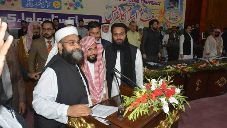 Pakistan Ulema Council Chairman Maulana Hafiz Muhammad Tahir Mehmood Ashrafi (left) and Imam-e-Kaaba Sheikh Abdullah Awad Al Juhany (centre) speak to the participants of an international conference in Islamabad April 14. [PUC]