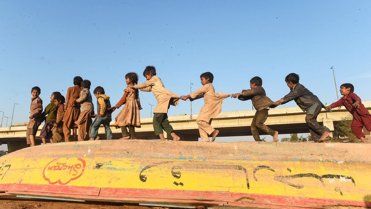 Children play on a boat alongside a river in Lahore January 9. [Arif Ali/AFP]