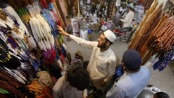 A young man May 6 sells caps and beads to worshippers at Qissa Khwani Bazaar in Peshawar. [Javed Khan]