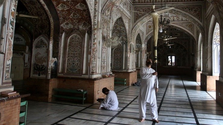 A man cleans the historic Mohabbat Khan Mosque in Peshawar May 6. [Javid Khan]