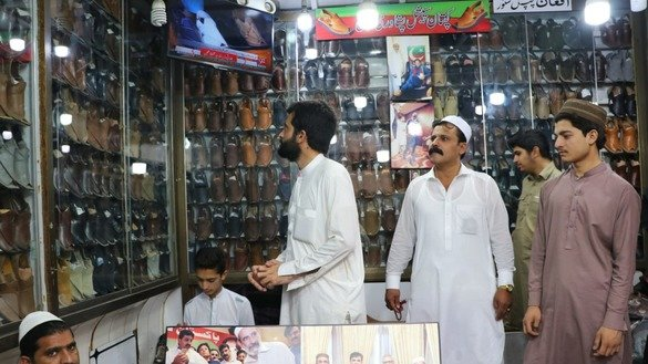 Customers select traditional chappal in a store in Peshawar on May 24. [Alamgir Khan]