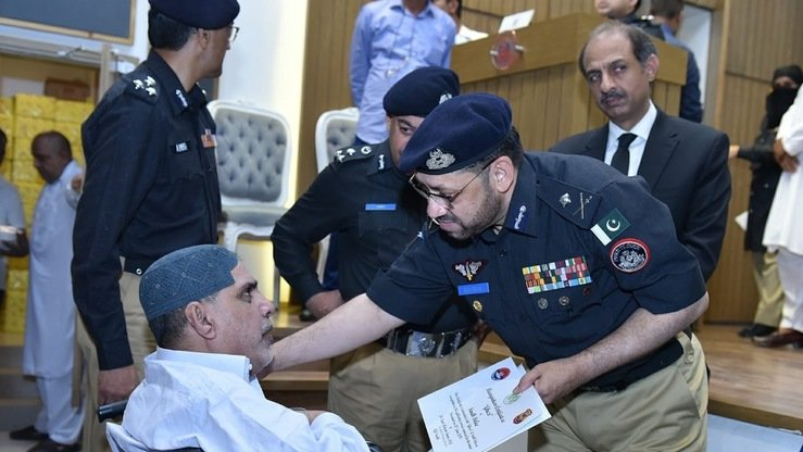 Sindh Police Chief Syed Kaleem Imam on June 21 meets with a wounded police officer in Karachi. [Karachi Police]