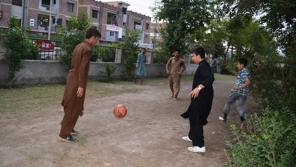Rashid Khan (left), 15, plays football with his friends May 3 in Peshawar. The new KP sports policy aims to promote sports in all of the province's schools. [Danish Yousafzai]